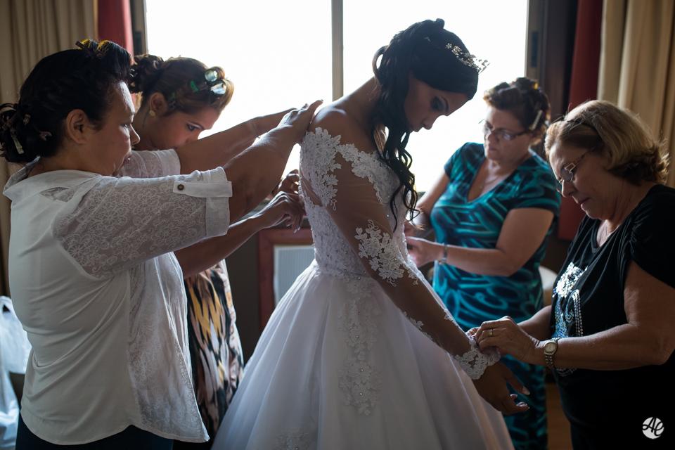 Noiva colocando o vestido de noiva e sendo ajudada pela mãe e pelas madrinhas durante o making of da noiva no hotel Novo Mundo
