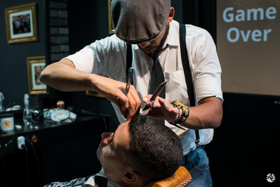Barbeiro cuidando dos últimos detalhes no corte de cabelo do noivo