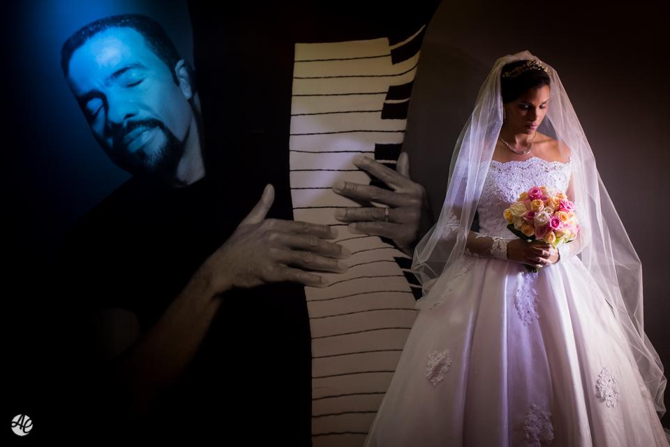Retrato da noiva diante de um painel com a imagem de uma pessoa tocando teclado
