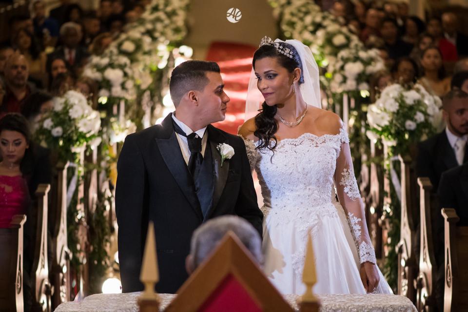 Casal de noivos se olham no altar diante do padre e perante aos convidados na cerimônia de casamento na Paróquia Santa Edwiges