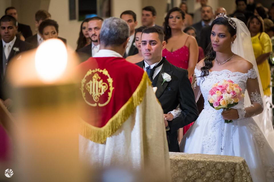 Noivo muito emocionado ao lado da noiva ouvindo as palavras do padre durante a cerimônia de casamento na Paróquia Santa Edwiges