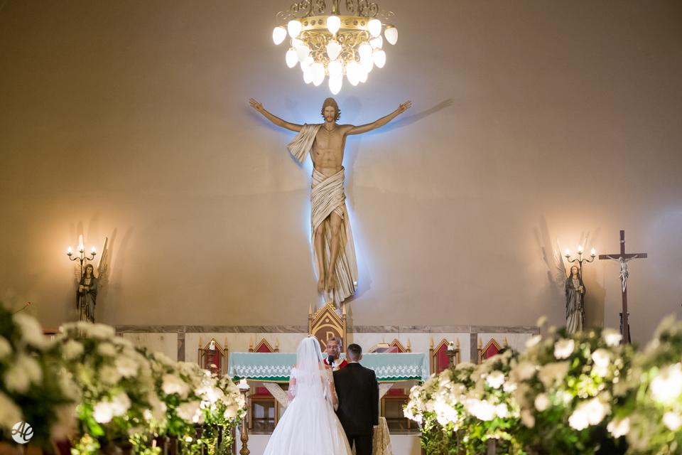 Noivos vistos de costas durante a cerimônia de casamento na Paróquia Santa Edwiges