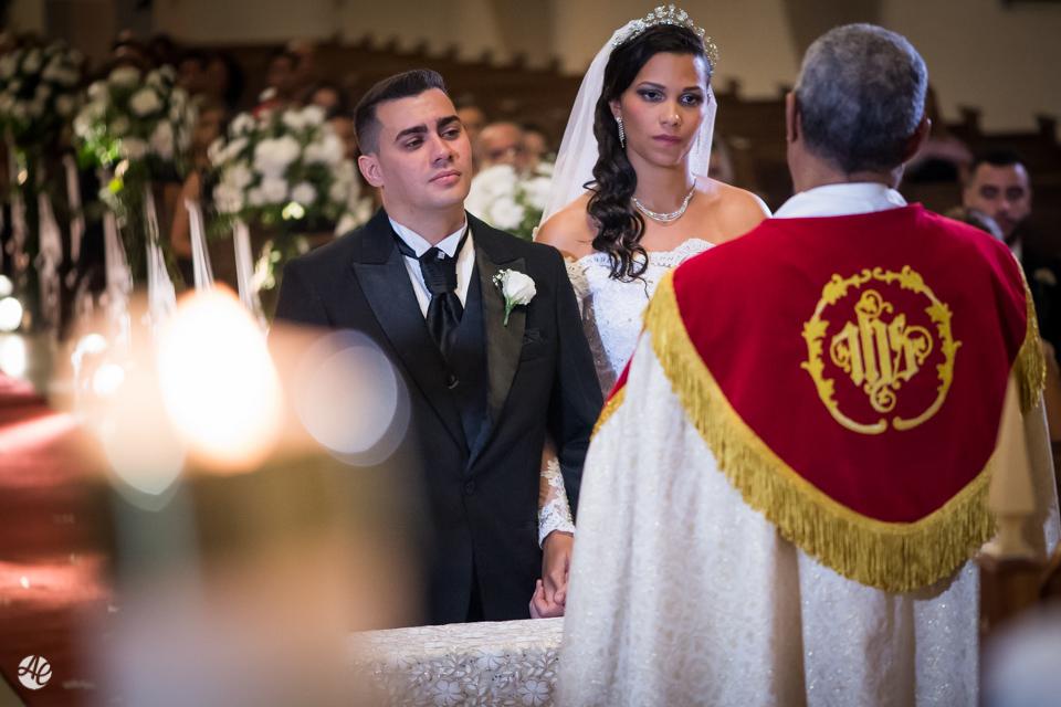 Noivos atentos ao padre na cerimônia de casamento na Paróquia Santa Edwiges