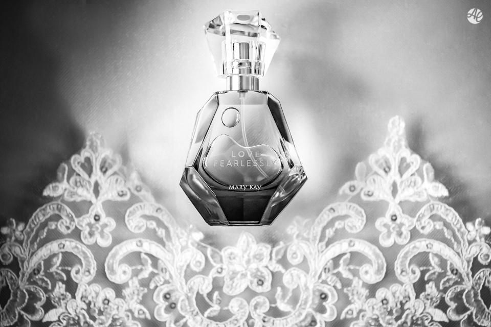 Perfume da noiva fotografado em cima da renda do vestido do casamento por Adriano Cardozo