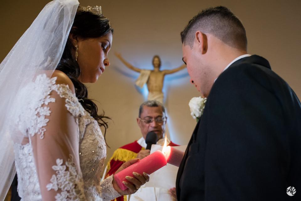 Noivos seguram velas acesas e ouvem atentamente ao padre na cerimônia de casamento na Paróquia Santa Edwiges