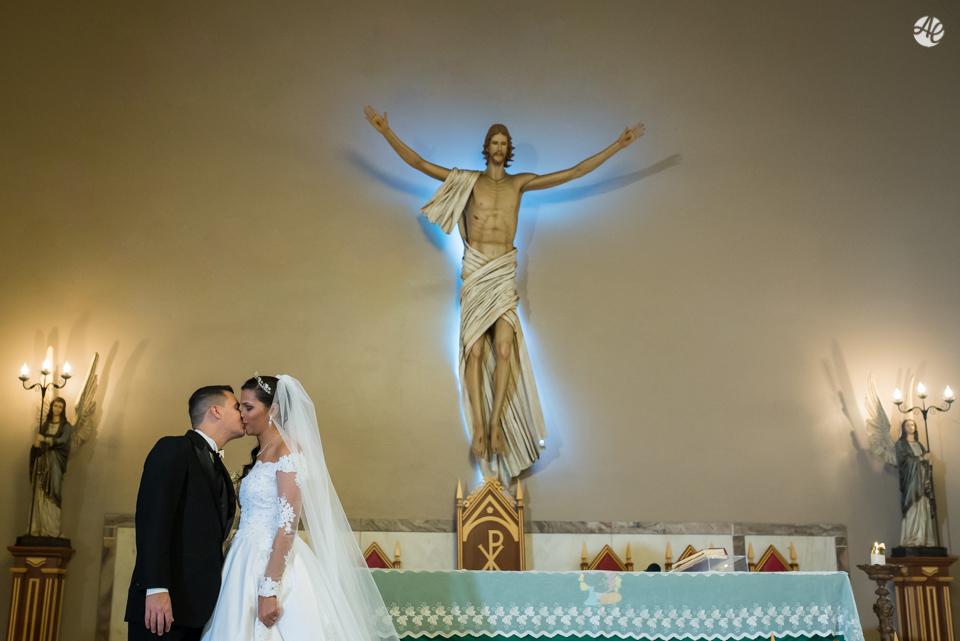 Casal de noivos se beijam no altar da Paróquia Santa Edwiges