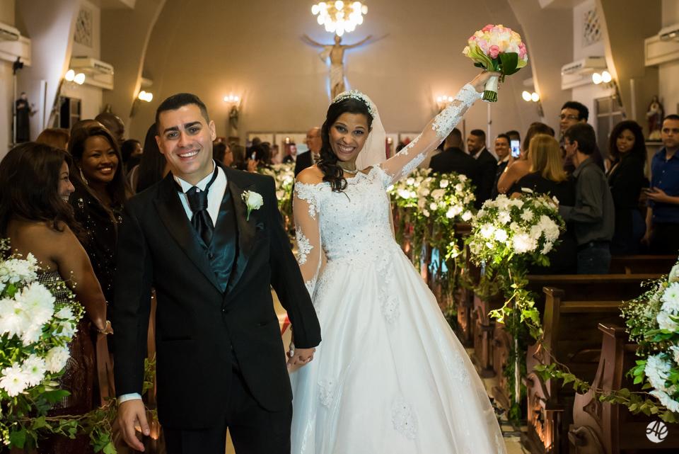 Noiva no corredor da igreja levanta o buquê comemorando a união do casal na Paróquia Santa Edwiges