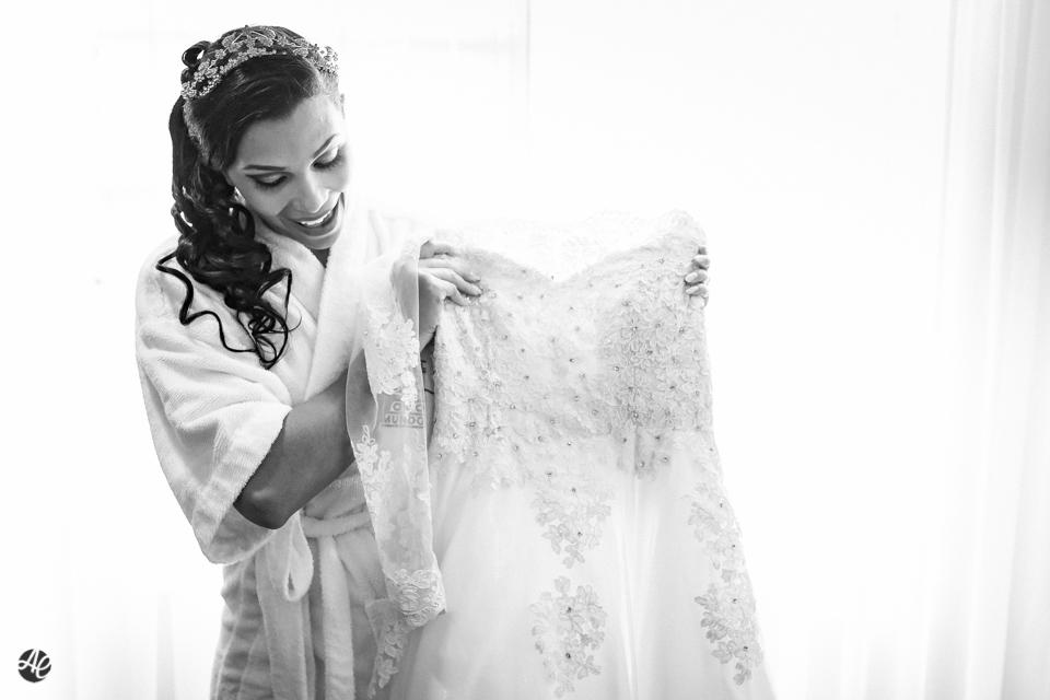 Noiva radiante segurando o vestido de noiva no making of da noiva no hotel Novo Mundo