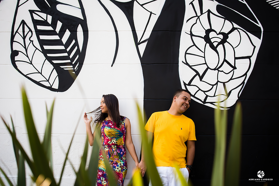 Casal encostado na parede grafitada em ensaio pré-wedding no Boulevard Olímpico no Rio de Janeiro por Adriano Cardozo