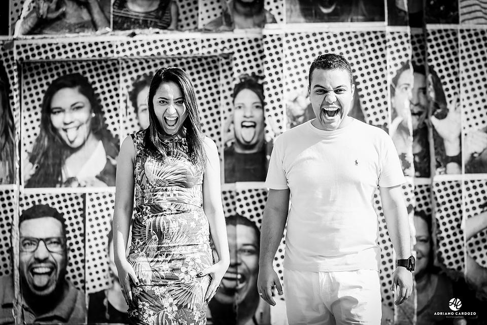 Noivos brincam fazendo imitação de imagens na parede ao fundo em Ensaio pré-wedding no Boulevard Olímpico