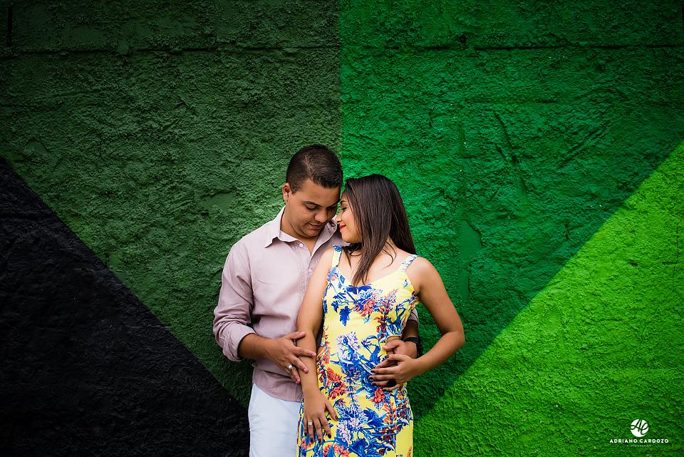 Fundo colorido destaca casal em conexão durante sessão fotográfica na Cidade Olímpica