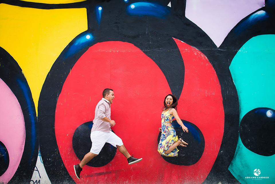 Casal comemora saltando em frente a grafite no Boulevard Olímpico no Rio de Janeiro