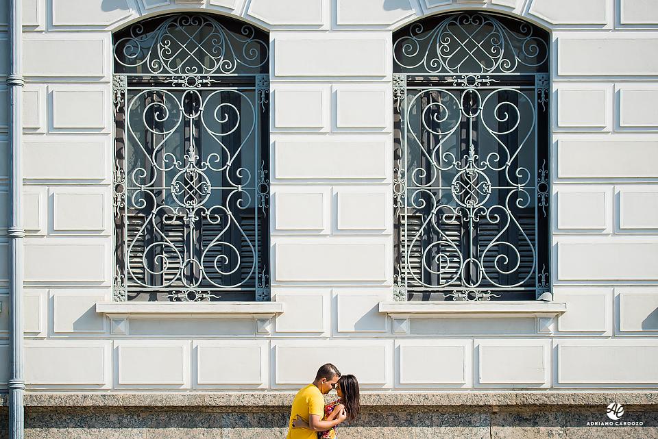 Casal em ensaio fotográfico Pré-Wedding tendo ao fundo duas belas janelas de uma antiga construção