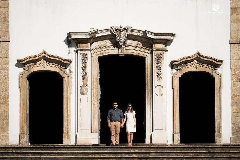 Thaís e Carlos em pé na frente da igreja durante seu ensaio pré-casamento