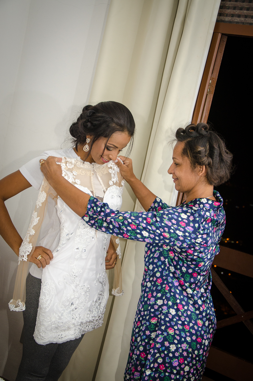 Mãe ajudando filha colocar o vestido do casamento