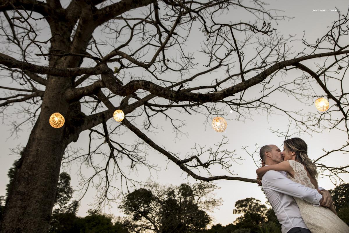 noivos se beijando luzes arvore