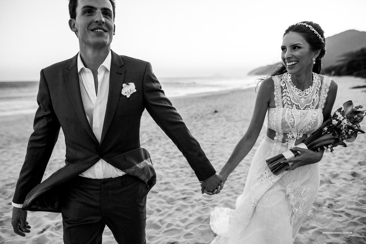 noivos caminhando na praia em maresias depois do casamento