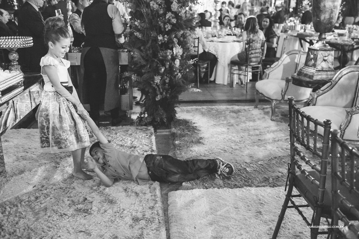 menina arrastando o menino pela festa do casamento