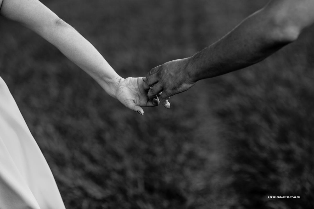 casal de mãos dadas com fundo desfocado