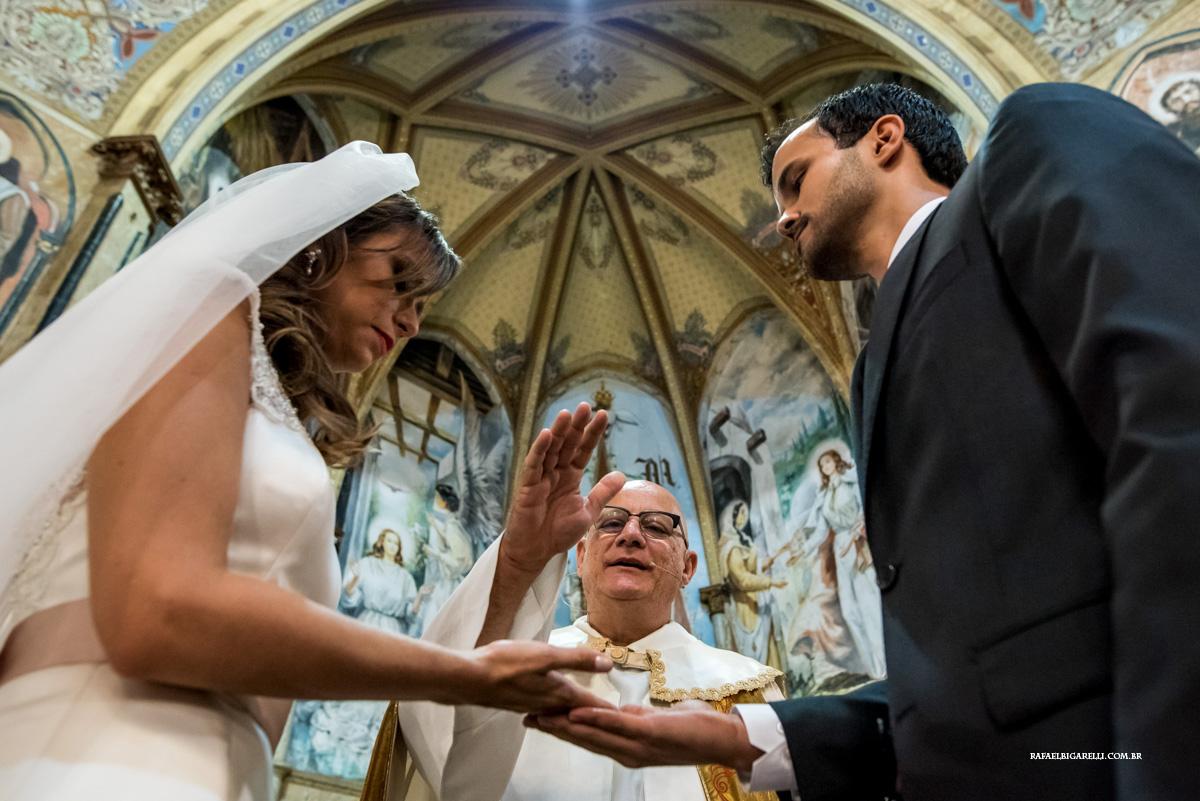 padre abençoa as alianças do casal