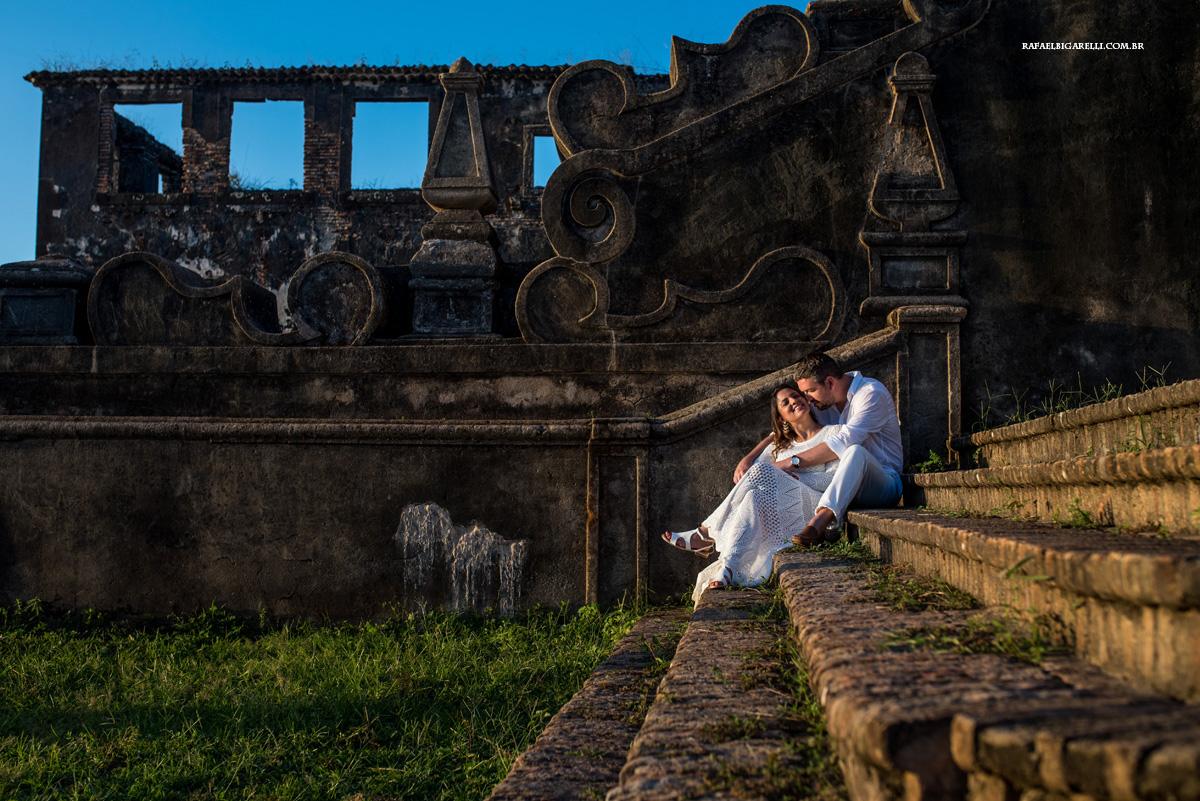 casal de noivos abraçados na escada da igreja