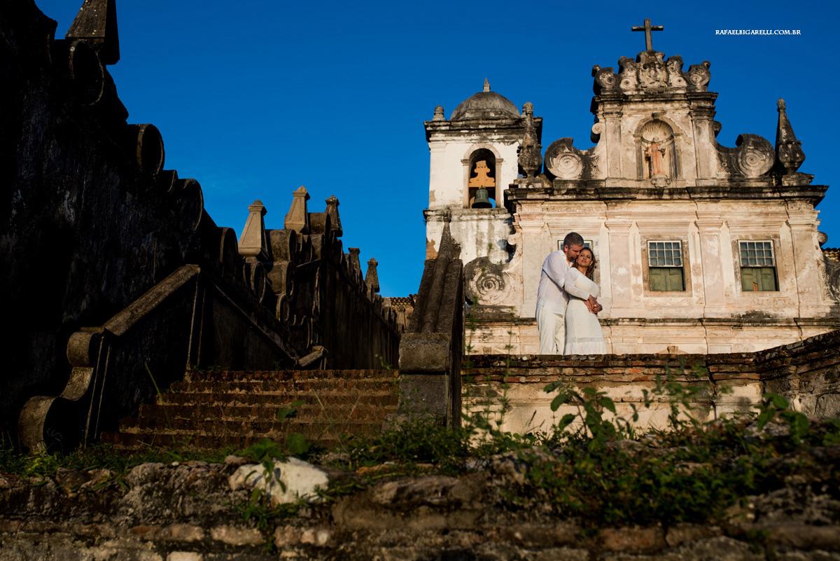 noivos se abraçam em frente a igreja