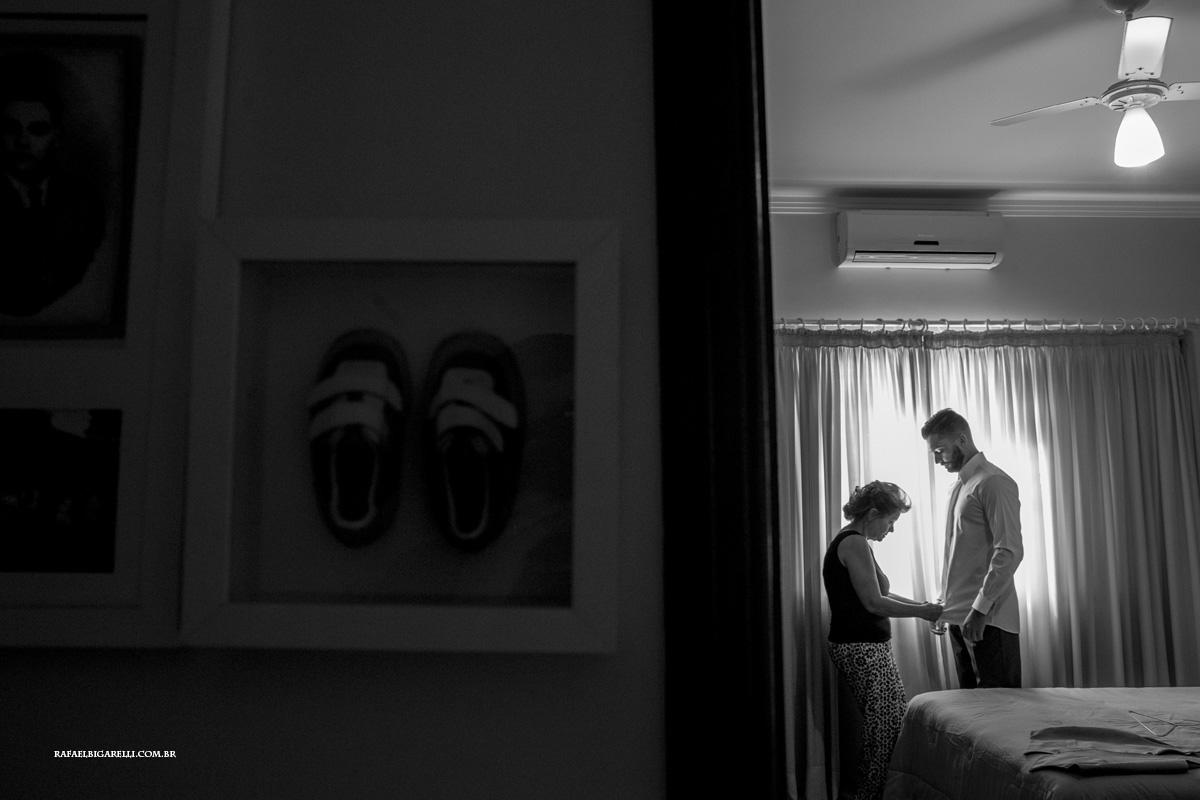mae ajuda noivo a arrumar seu traje para o casamento
