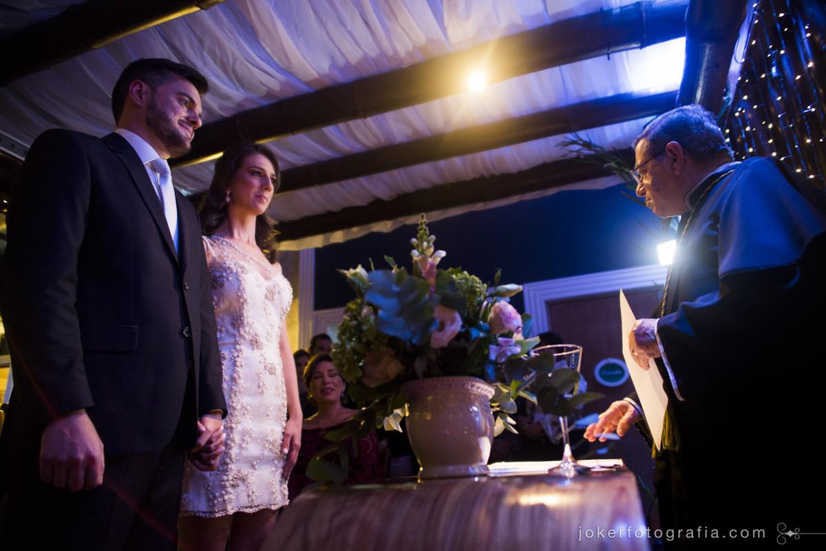 noivos no altar durante celebração de casamento