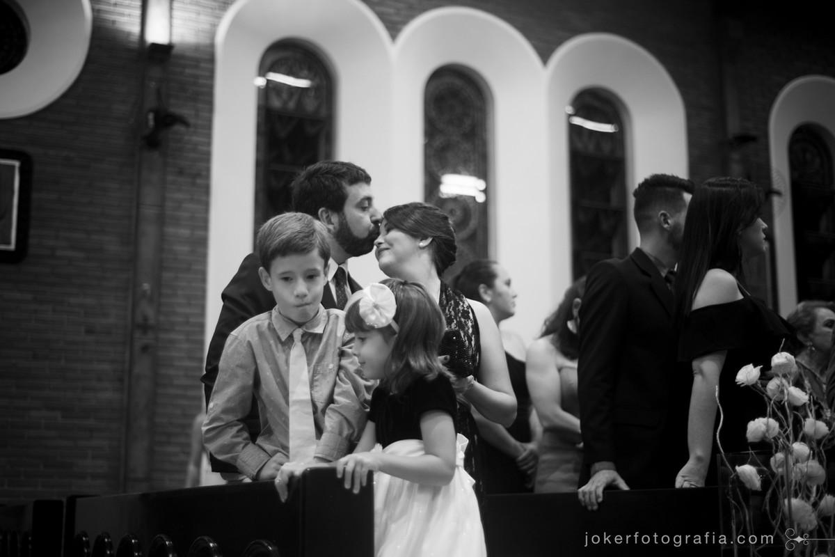fotógrafo capta momentos espontâneos dos convidados durante a cerimônia e flagra beijo carinhoso de casal de padrinhos