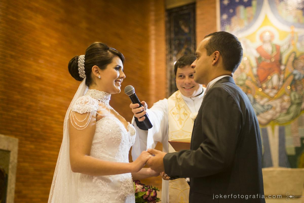 padre sorridente em cerimônia de casamento na paróquia cristo rei em curitiba