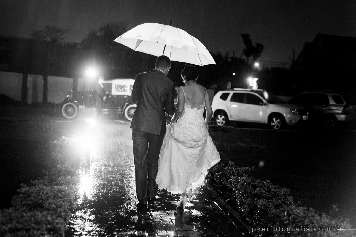 chuva no dia do casamento noivos saindo com guarda chuva
