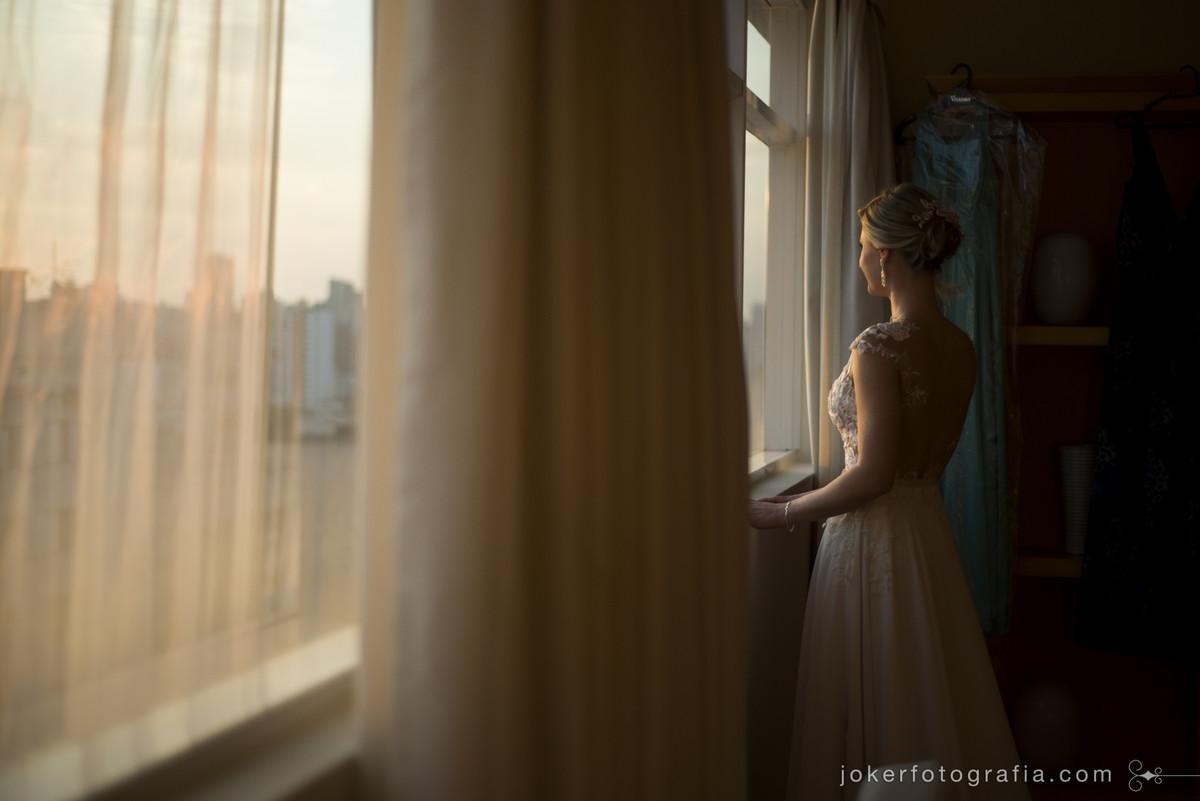 noiva olhando o por do sol pela janela do quarto