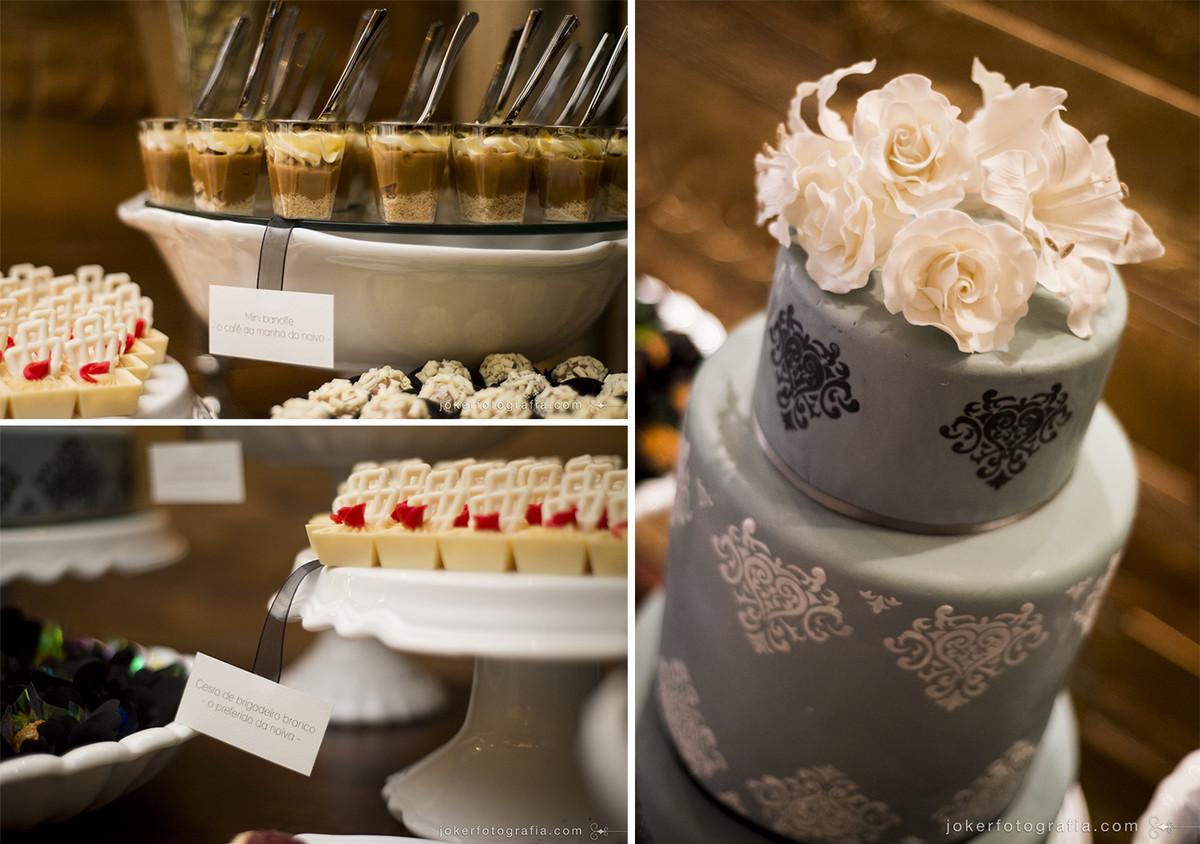 docinhos de casamento com tags especiais ao lado de bolo azul feito pelos noivos