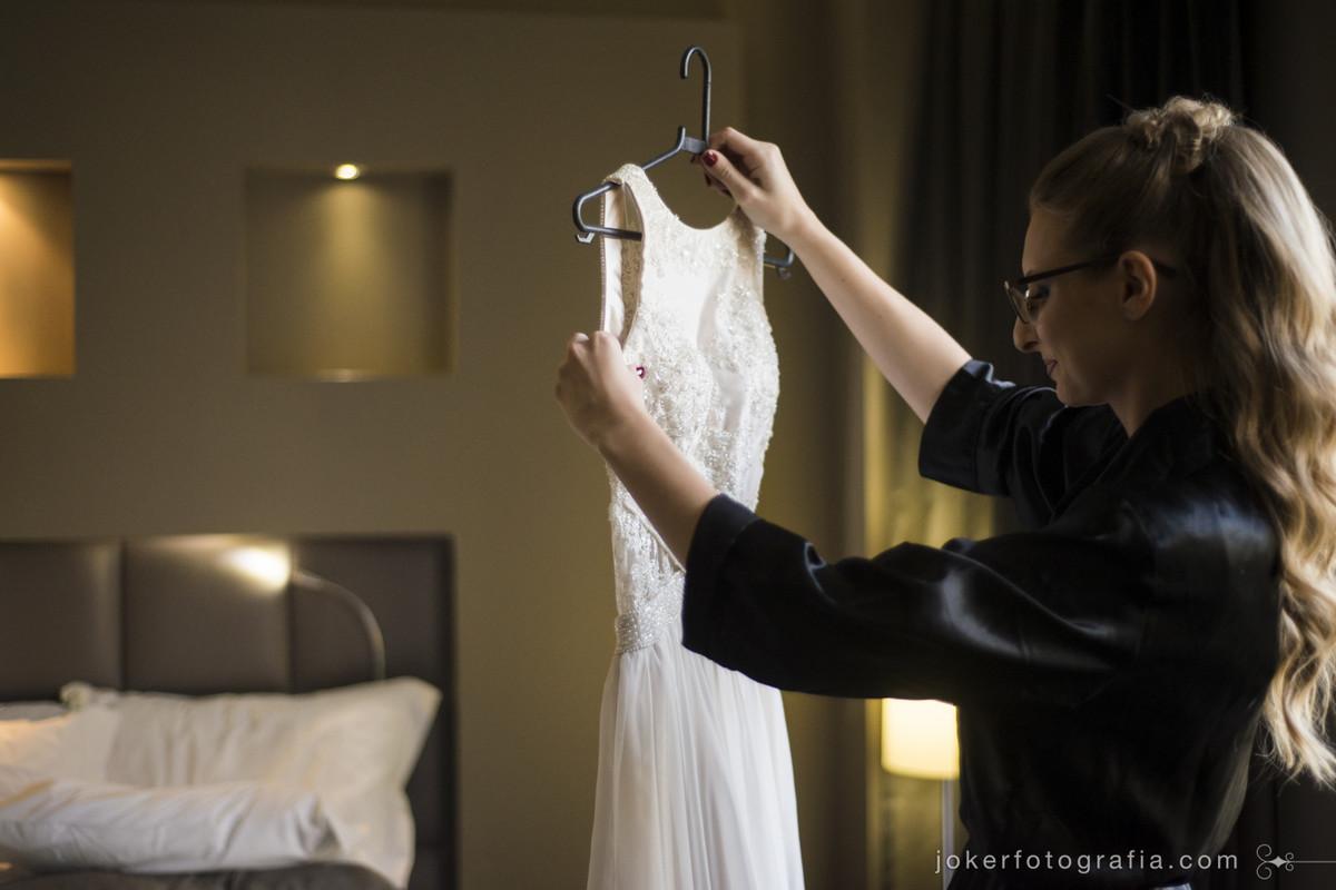 encantada olhando seu vestido de noiva feito sob medida