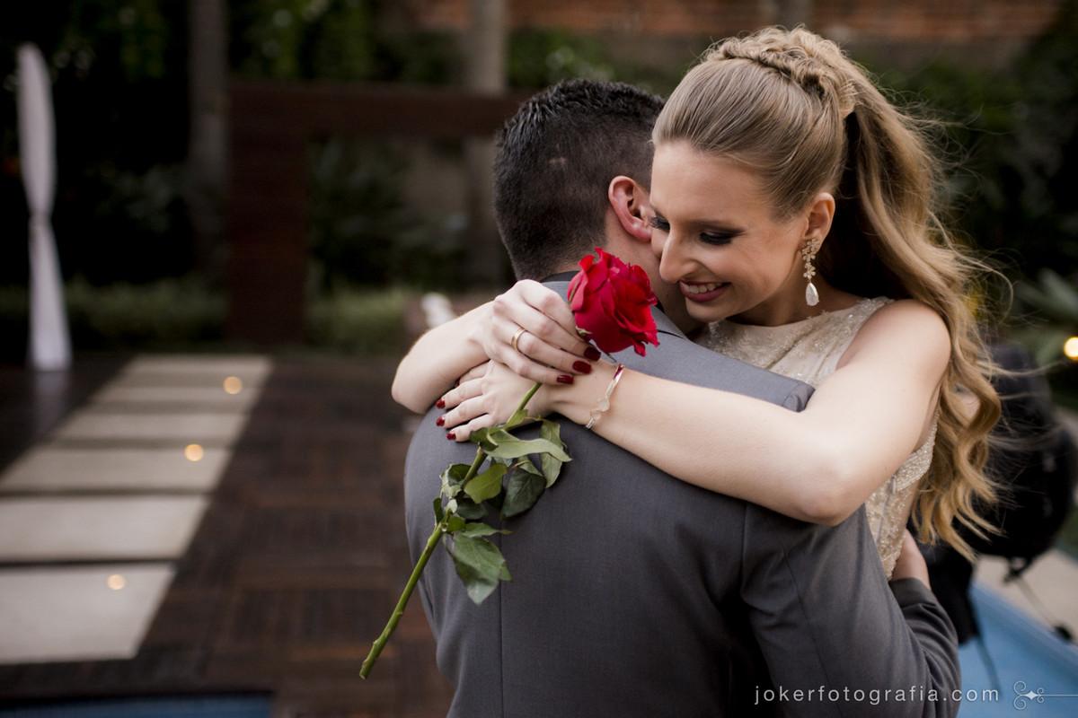 fotógrafo de casamento capta o primeiro abraço de noivos e ela segurando uma rosa
