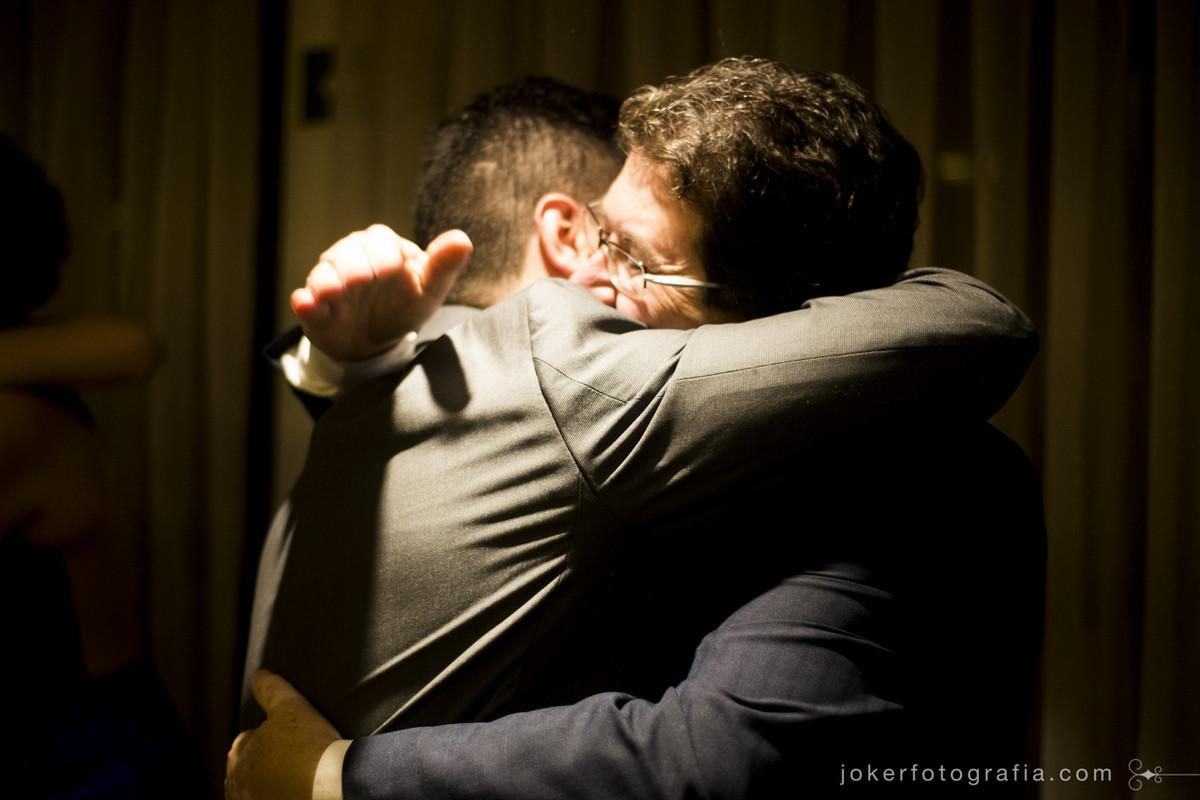 pai do noivo emocionado abraça o filho no dia do casamento