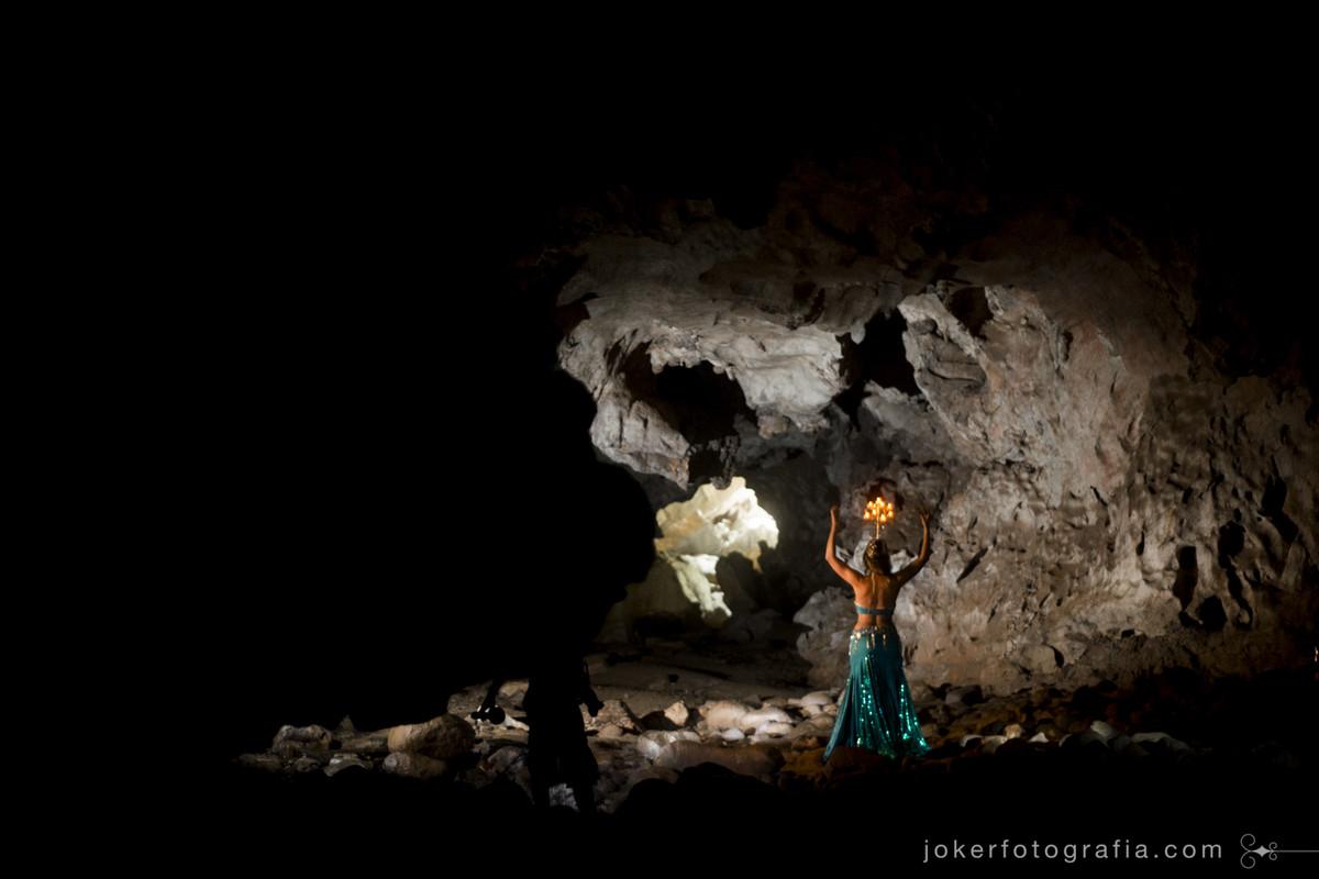 inspiração para dança do ventre, dançarina usando candelabro faz fotos dentro de uma caverna