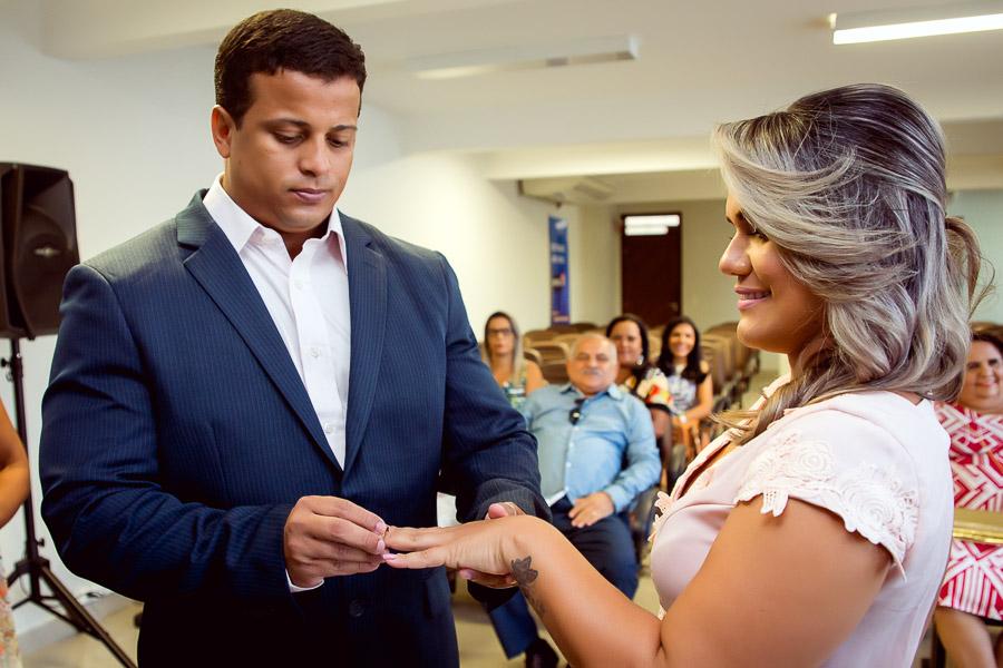 noivo colocando aliança no dedo da noiva