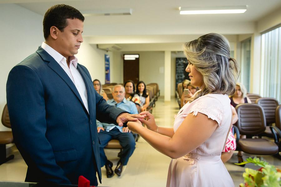 noiva colocando aliança no dedo do noivo