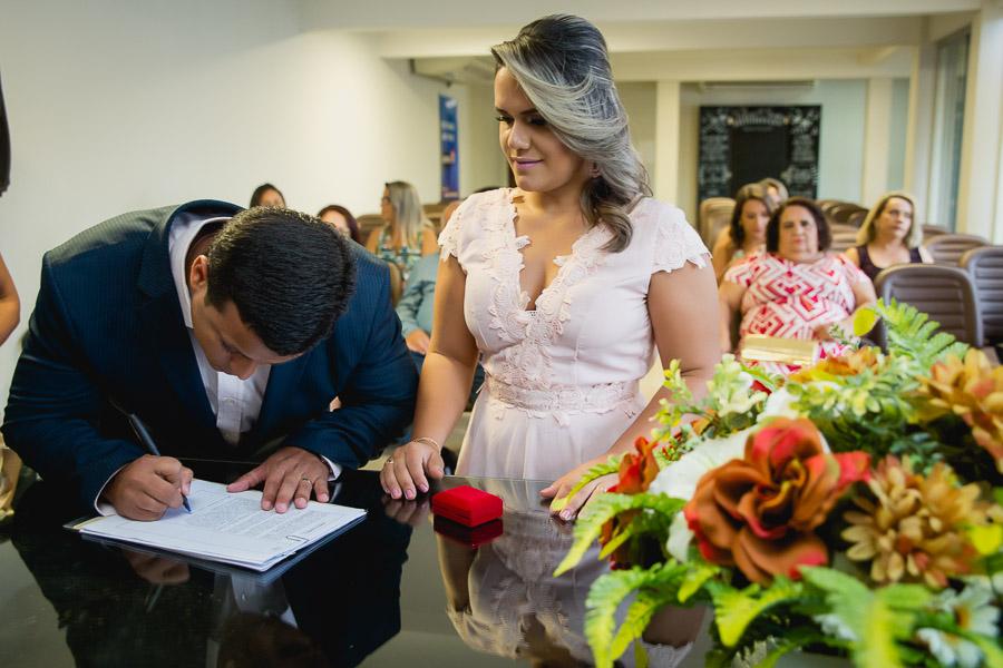 noivo assinando certidão e noiva olhando