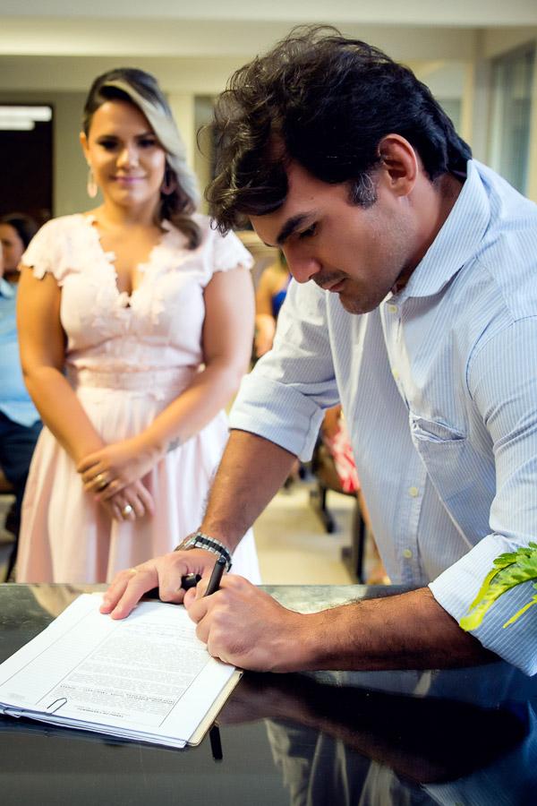 padrinho da noiva assinando certidão e ela olhando