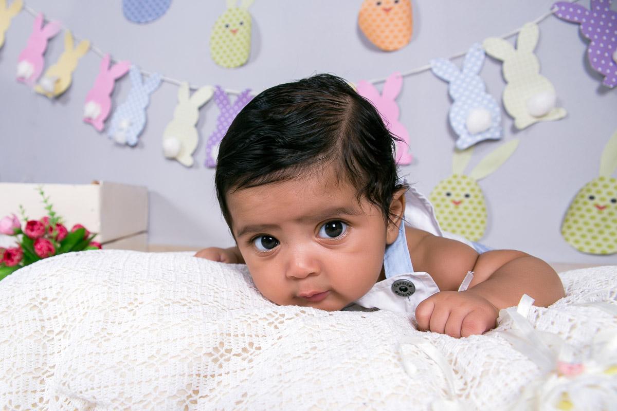 Acompanhamento infantil realizado em estudio com tema de Páscoa. BebÊ de bruços em almofadas coberto com tecido. Cenario com bandeirolas na parede em formato de coelho, caixote com coelho dentro, pegadas de coelhos no chão, cest
