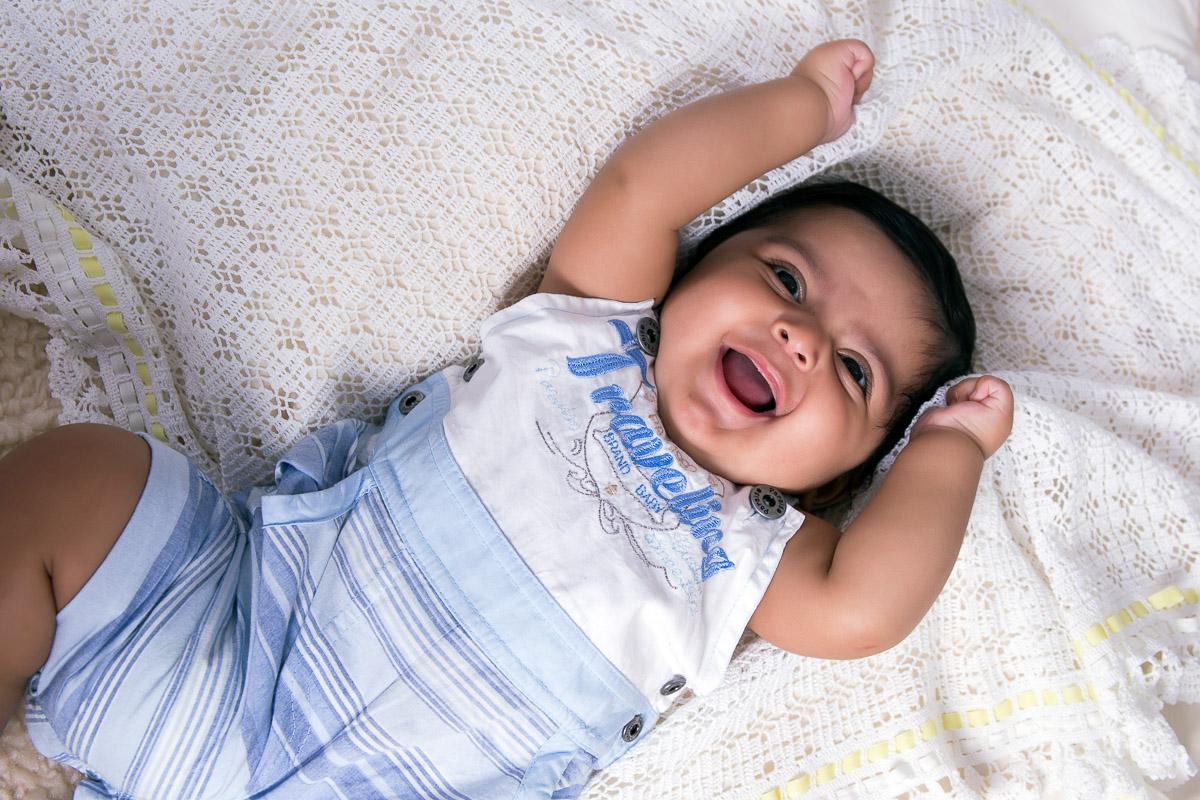 Acompanhamento infantil realizado em estudio com tema de Páscoa. BebÊ deitado em almofadas coberto com tecido. Cenario com bandeirolas na parede em formato de coelho, caixote com coelho dentro, pegadas de coelhos no chão, cestinha com