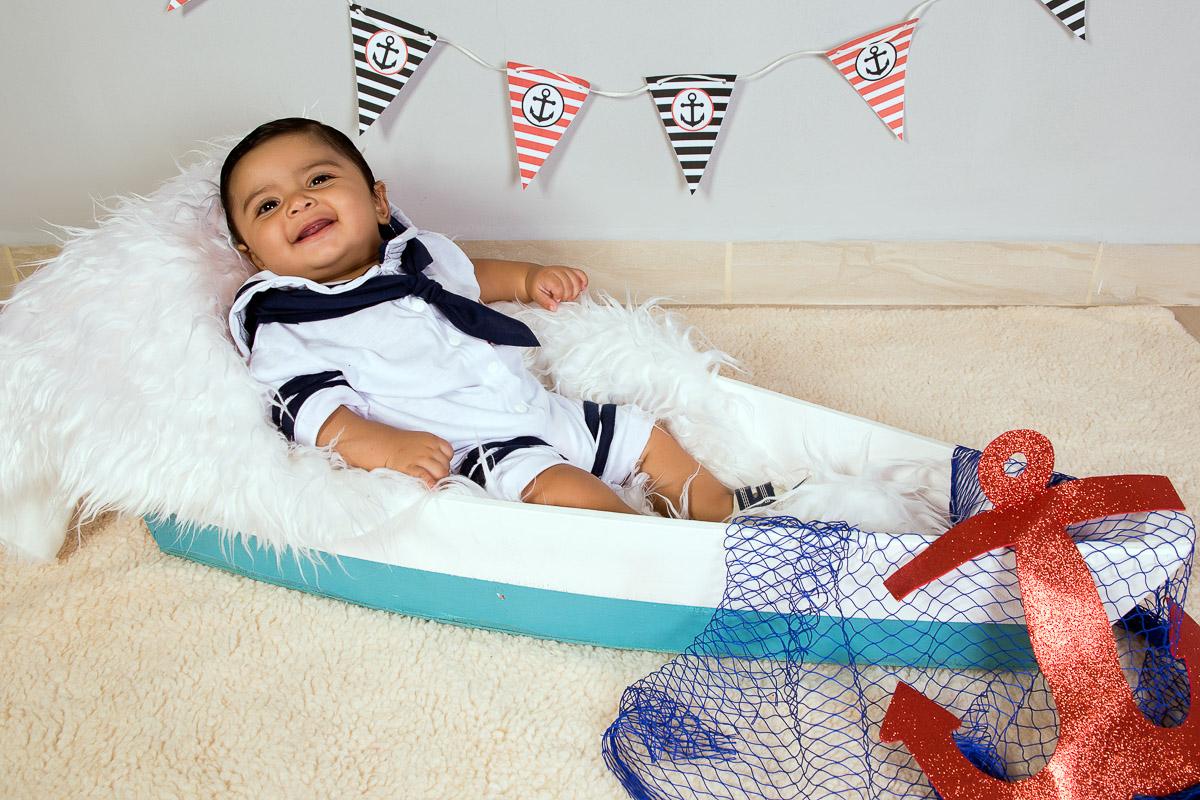 Acompanhamento infantil realizado em estudio com menino de 4 meses e tema de marinheiro. BebÊ sentado dentro de barco feito de mdf, vestido com roupa de marinheiro azul e branca.. Cenario com bandeirolas na parede nas cores vermelha e azul com &acir