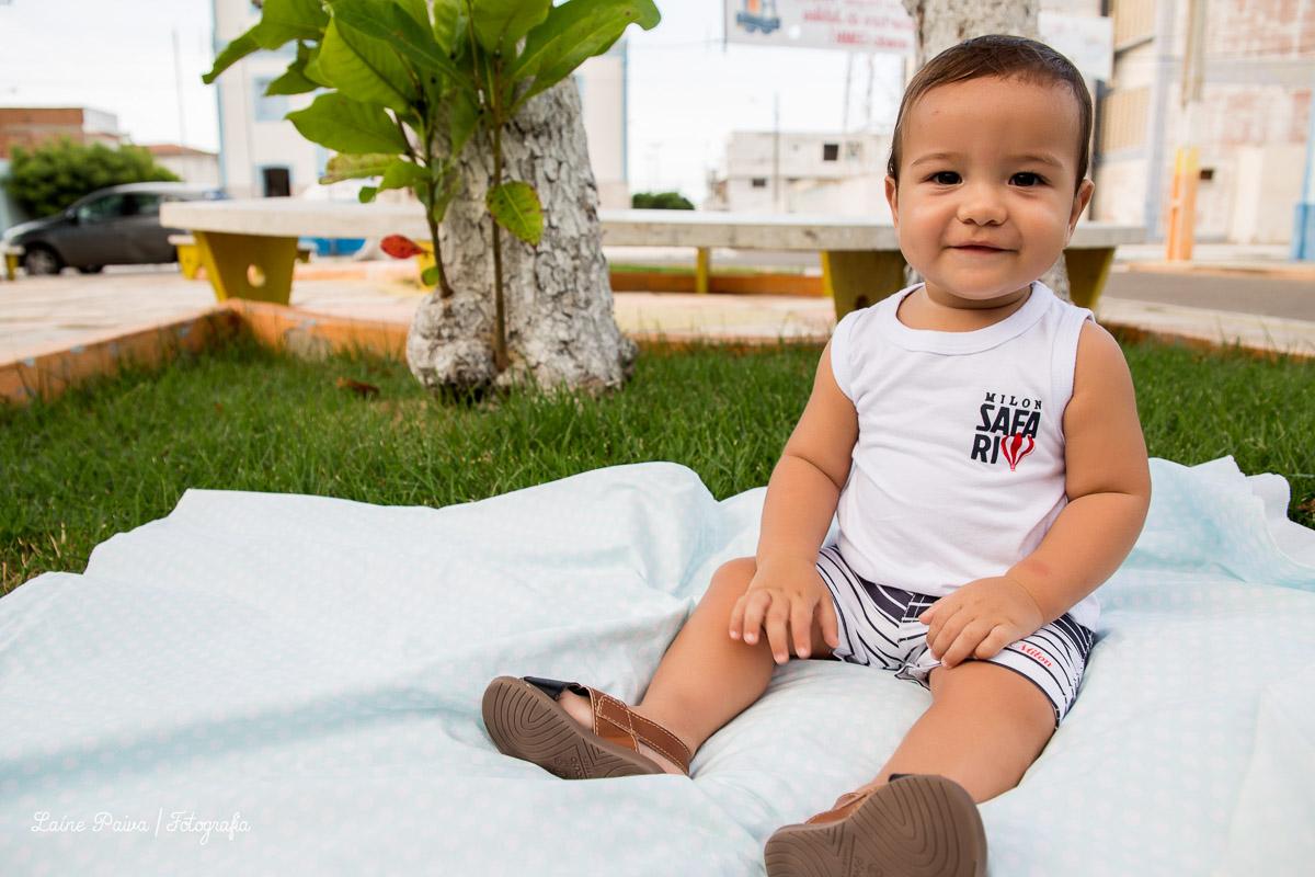 Fotografia infatil, acompanhamento de menino com 8 meses. Tema pique nique. Bebê sentado em tecido colocado em uma grama de uma pracinha na cidade de Macau/RN.