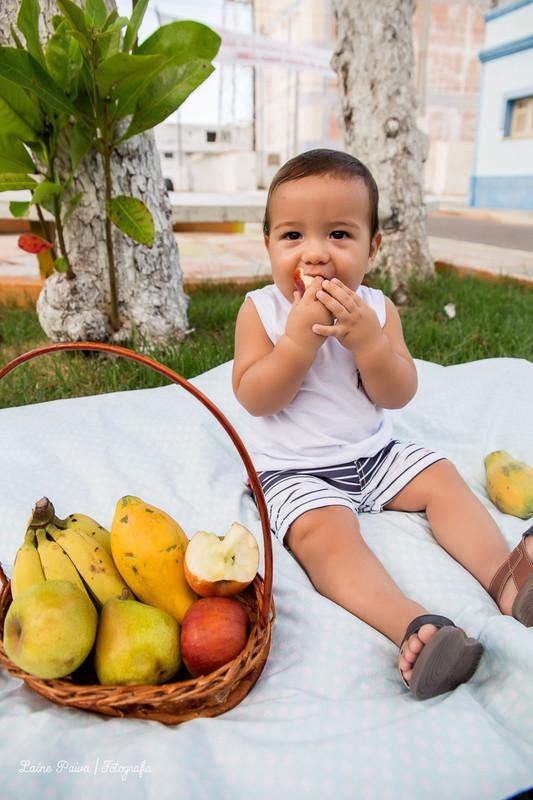 Fotografia infatil, acompanhamento de menino com 8 meses. Tema pique nique. Bebê sentado em tecido colocado em uma grama de uma pracinha na cidade de Macau/RN. Cestas com frutas ao lado do bebe e ele mordendo uma.