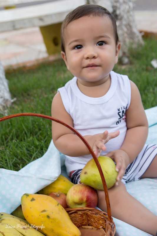 Fotografia infatil, acompanhamento de menino com 8 meses. Tema pique nique. Bebê sentado em tecido colocado em uma grama de uma pracinha na cidade de Macau/RN. Cestas com frutas ao lado do bebe e ele com uma na mão.