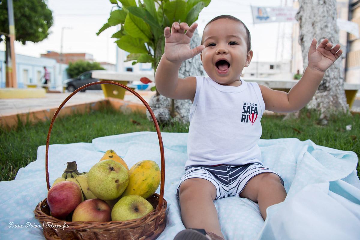 Fotografia infatil, acompanhamento de menino com 8 meses. Tema pique nique. Bebê sentado em tecido colocado em uma grama de uma pracinha na cidade de Macau/RN. Cestas com frutas ao lado do bebe cantando.