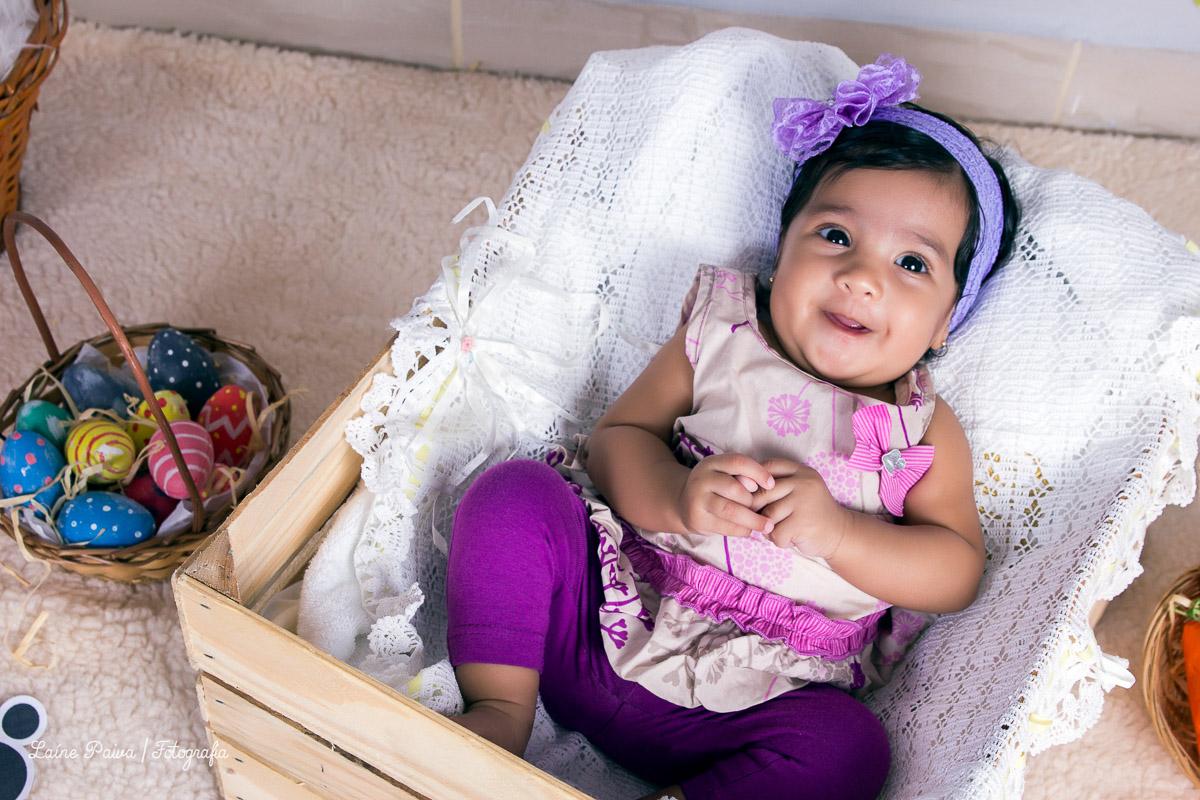 bebe de 3 meses fazendo acompanhamento deitada dentro de um caixote de madeira
