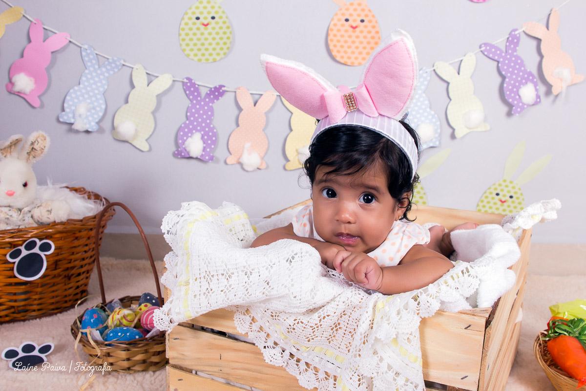 Bebe de 3 meses, menina, acompanhamento infantil com o tema de pascoa, deitada de bruços dentro de um caixote de madeira com tecido dentro. Cenario com bandeirolas de coelhos, pegadas no châo, cesto com ovos feito de gesso, tudo para compor o
